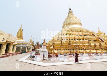 Bagan, Myanmar - March 2019: Buddhist monk walking next to Shwezigon Paya golden temple. - Stock Photo