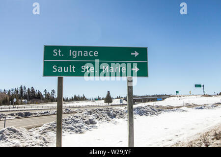Upper Peninsula Michigan Winter. Interstate 75 sign for the towns of St. Ignace and Sault Ste Marie Mich in the UP of Michigan on a sunny winter day - Stock Photo