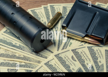 Rifle barrel, suppressor and cartridges on dollars. Concept for crime, contract killing, paid assassin, terrorism, war, global arms trade, weapons - Stock Photo