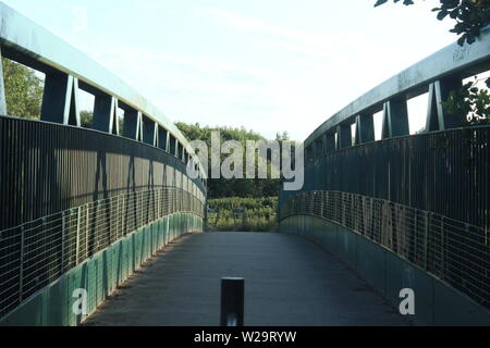 Image of green walkway bridge with bushes and trees in the distance over a lake on a sunny, clear day - Stock Photo