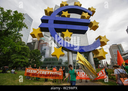Frankfurt, Germany. 06th July, 2019. Protesters stand with banners in front of the large Euro sign. Over 1,000 people marched through Frankfurt, to call for save refugees routes, an end to the criminalisation of sea rescue and a provision of save harbours for refugees in Europe. This protest was part of a German wide Seebrucke protest under the slogan of 'State of emergency of humanity', which took place  after German Sea-Watch 3 captain Carola Rackete was arrested in Italy for rescuing refugees in the Mediterranean and bringing them to Italy. Credit: PACIFIC PRESS/Alamy Live News - Stock Photo