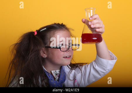 MR - Science Geek Young Girl / Female in glasses Age 7 - child measuring red liquid chemical in borosilicate science beakers on yellow background - Stock Photo