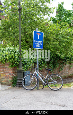 Ladies bicycle chained to a metal road sign post - Stock Photo