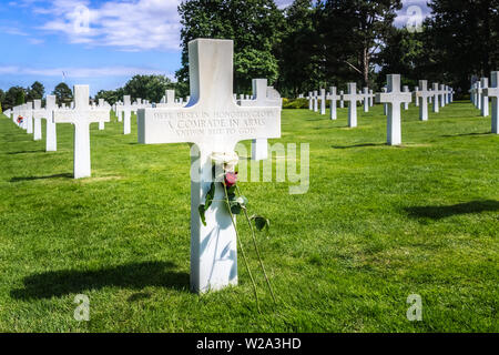 Unknown soldier grave with white cross and flowers at D-Day Normandy American Cemetery, Colleville-sur-Mer, France. - Stock Photo