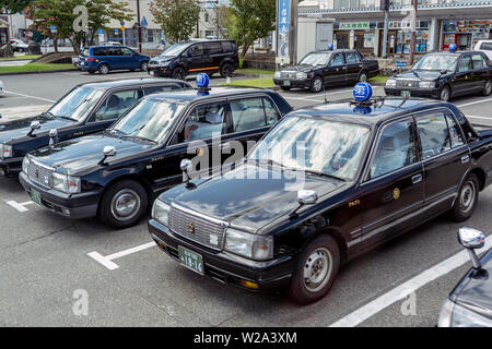 Row Of Black Retro Japanese Taxi Cars. Taxi Park In Tokyo. Taxi Drivers Are Waiting For Passengers. - Stock Photo
