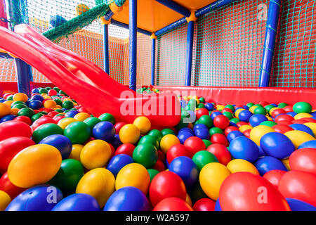 Colored plastic balls in pool of game room. Swimming pool for fun and jumping in colored plastic balls - Stock Photo