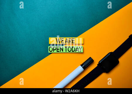 We Are Open Today text on top view color table background. - Stock Photo