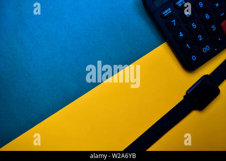 Smart Watch and Calculator text on top view color table background. - Stock Photo