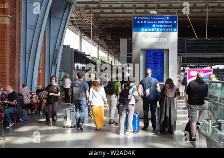 St Pancras London UK; rail passengers looking at the train departure board on the platform, St Pancras International train station London UK - Stock Photo
