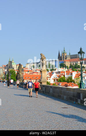 Prague, Czech Republic - June 27th 2019: Tourists on beautiful Charles Bridge in the center of Czech capital. Prague Castle in background. Famous tour - Stock Photo