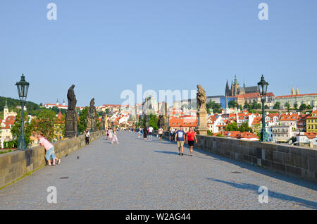 Prague, Czech Republic - June 27th 2019: People walking on famous Charles Bridge over Vltava river in the histrorical center of the Czech capital. Pra - Stock Photo