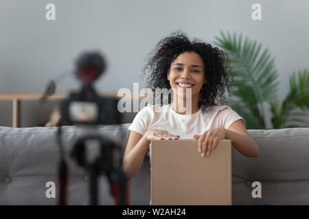 Happy african young woman blogger open parcel shooting video blog - Stock Photo
