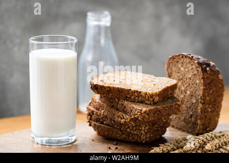 Rye bread with sunflower seeds and glass of milk on rustic wooden table - Stock Photo