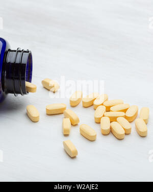 Light yellow pills lie on a white table next to the package. Concept of vitamin elements and health programs. Advertising space. - Stock Photo