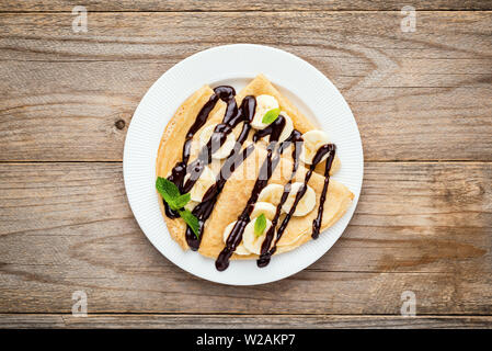 Crepes or blini with banana slices and chocolate sauce on white plate, wooden planks background. Top view - Stock Photo