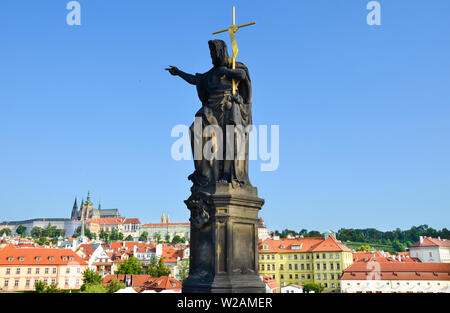Religious statue on the edge of famous Charles Bridge in Prague, Czech Republic. Prague Castle and historical old town in background. Blue sky. Praga, Czechia. Beautiful cities. Cityscape. - Stock Photo