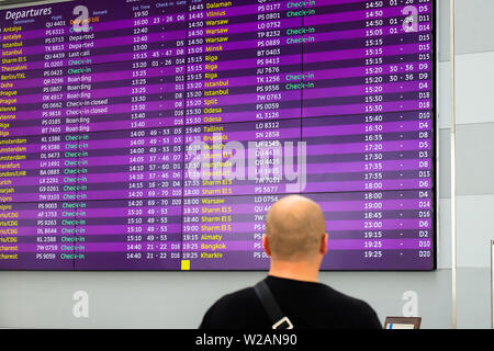 A man is standing in front of information board for arrivals and departures. Information stand at the airport, railway station, bus station, travel - Stock Photo