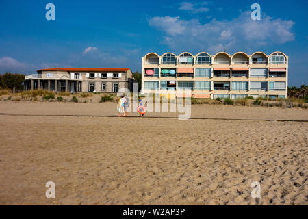 Family walking along the beach boardwalk in front of some 1980's holiday apartments - Stock Photo