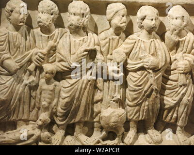 Six sculpted figures on the side of a marble sarcophagus; one of the exhibits at the Montemartini museum from excavations of Ancient Rome - Stock Photo