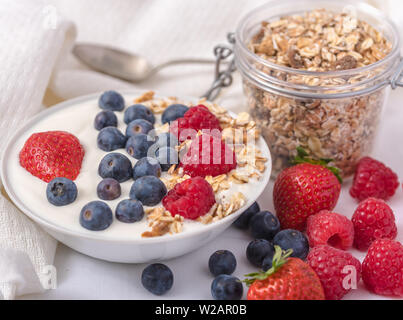 White yogurt in bowl with oatmeal and strawberries, blueberries and raspberries on the top on white background. - Stock Photo