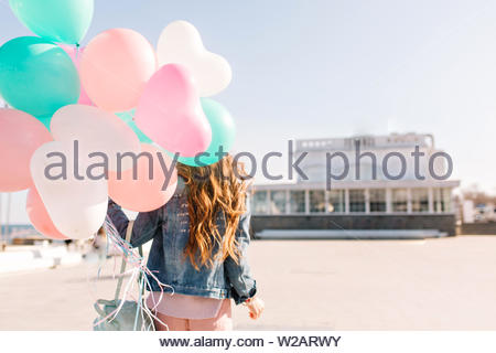 Stylish long-haired woman enjoys life and spending time outside holding birthday gift on the city background. Curly girl in denim jacket with backpack going to event and carrying helium balloons - Stock Photo