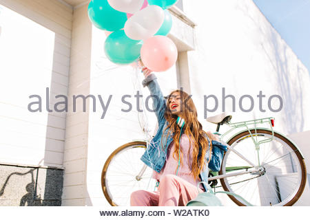 Stylish charming girl with brown hair rejoices life, raising hand with a bunch of colored balls. Adorable young woman in pink clothes sitting outside after bike ride around the city in sunny morning. - Stock Photo