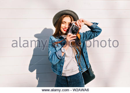 Tired female photographer in trendy denim outfit takes latest pictures standing outside. Portrait of charming brunette girl in hat and stylish jacket posing with prosessional camera in front of wall - Stock Photo