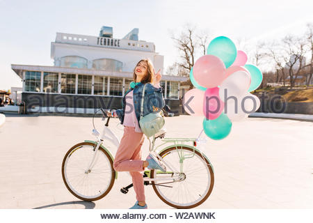 Happy girl with headphones wearing stylish clothes, going to bicycle ride around the city in sunny day. Adorable young woman holding cute backpack gladly posing with bunch of balloons and peace sign - Stock Photo