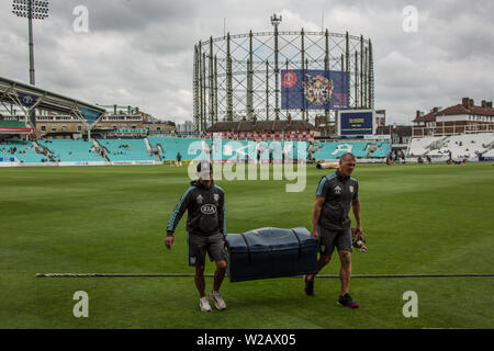 London, UK. 7 July, 2019. Alec Stewart (right) helps remove warm-up gear from the pitch, with The old Gasometer with ICC Cricket World Cup branding in the background, ahead of the first day of the Specsavers County Championship game between Surrey and Kent at the Kia Oval. David Rowe/Alamy Live News - Stock Photo