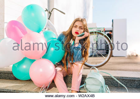 Cute long-haired girl with face expression of discontent waiting for friends who are late, holding helium balloons. Portrait of unhappy young woman in pink pants sitting on steps in front of bicycle - Stock Photo