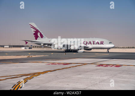 A Qatar Airways Airbus A380-800 superjumbo jet accelerates for takeoff at Hamad International Airport, Doha, State of Qatar - Stock Photo