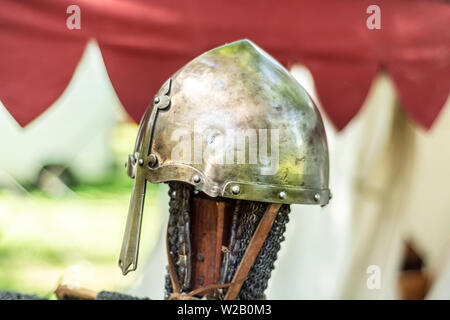 Knightly medieval metal helmet on the stand. Old dark ages armor and equipment for knights head protection in battle. Historical and medieval concept - Stock Photo