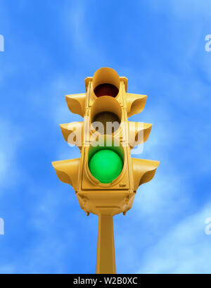 Upward view of tall vintage yellow traffic signal with green light on blue sky background - Stock Photo