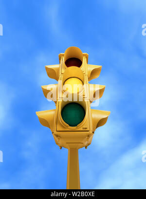 Upward view of tall vintage yellow traffic signal with yellow light on blue sky background - Stock Photo