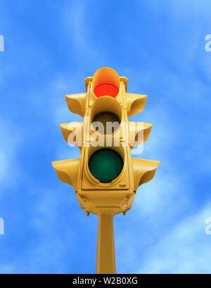 Upward view of tall vintage yellow traffic signal with red light on blue sky background - Stock Photo
