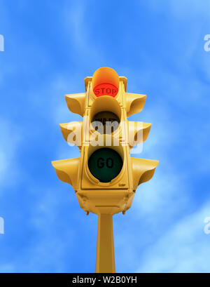 Upward view of  tall vintage yellow traffic light with red STOP signal on blue sky background - Stock Photo