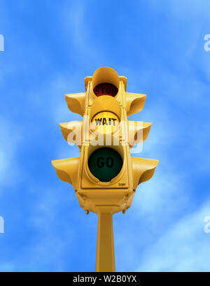 Upward view of  tall vintage yellow traffic light with yellow WAIT signal on blue sky background - Stock Photo
