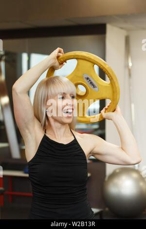 Kharkiv, Ukraine - February 17, 2019: Young blonde female athlete doing weightlifting exercises - Stock Photo