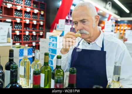 worker smelling cork from wine bottle - Stock Photo