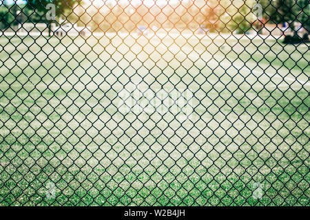 Closeup of black metal netting wire mesh fence against green field meadow. Texture pattern surface background of  chain link wire-mesh rabitz. - Stock Photo