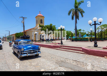 Trinidad, Cuba - June 6, 2019: View of an Old Classic American Car in the streets of a small Cuban Town during a vibrant sunny day.