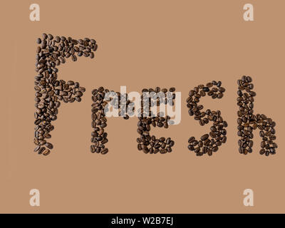 The word 'FRESH' spelled out with coffee beans on a tan background with copy space. - Stock Photo