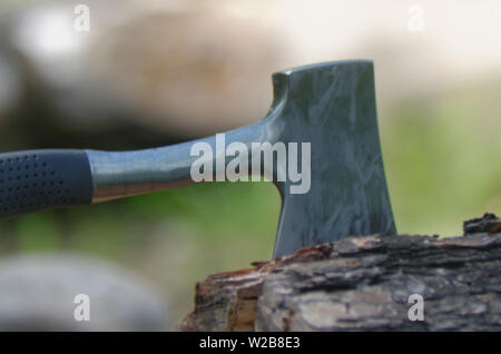 A hatchet with blade buried in a log after being used to chop fire wood - Stock Photo