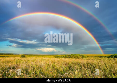 Rainbow over stormy sky in countryside at summer day - Stock Photo