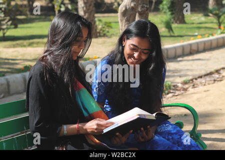 Two young beautiful Indian women enjoying by reading a book together sitting on a green garden bench along the road in a bright sunny day outdoor - Stock Photo