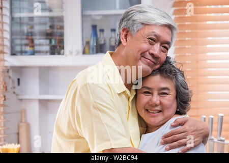 asian senior couple embrace togerther and looking at camera and smiling in kitchen at home.Happy aging at home concept - Stock Photo