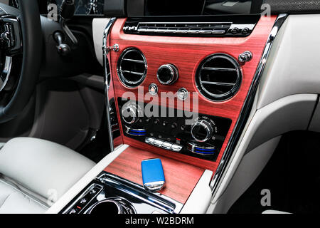 Modern luxury car white leather interior with natural wood panel. Part of leather car seat details with stitching. Interior of prestige modern car. Wh - Stock Photo