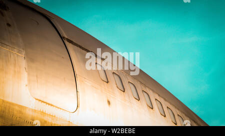 modern airplane parked on airport runway isolated on blue sky background side view of white jet engine passenger - Stock Photo