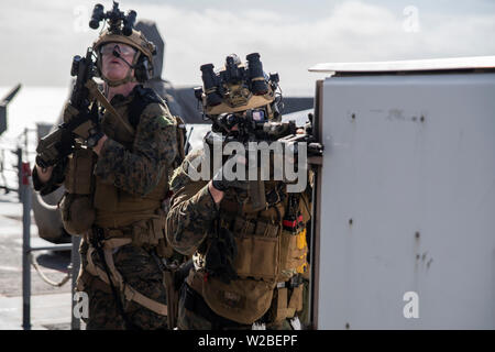 Force Reconnaissance Marines with Maritime Raid Force, 31st Marine Expeditionary Unit, provide security during a visit, board, search and seizure exercise aboard the amphibious dock landing ship USS Ashland (LSD 48), underway in the Coral Sea, June 29, 2019. Ashland, part of the Wasp Amphibious Ready Group, with embarked 31st MEU, is operating in the Indo-Pacific region to enhance interoperability with partners and serve as a ready-response force for any type of contingency, while simultaneously providing a flexible and lethal crisis response force ready to perform a wide range of military ope - Stock Photo