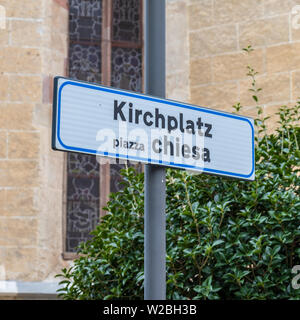 Bilingual Signs lettering Church Square, in german, Kirchplatz, and italian, piazzo chiesa. Church wall in background. - Stock Photo